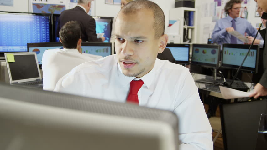 Young and ambitious stock market trader is doing a deal over the phone in a busy office filled with computers. The rest of his team are hard at work in the background.  #3676688