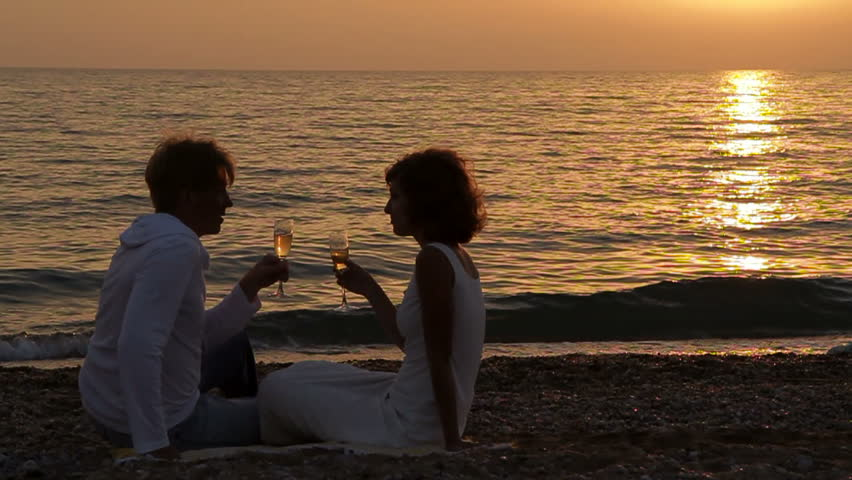 Silhouette of a couple on the beach having champagne at sunset.