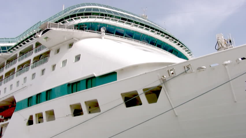 The camcorder carries along the side of a large snow-white cruise ship from stem