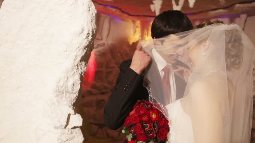 Young couple kissing hiding behind a veil in therapeutic salt cave.