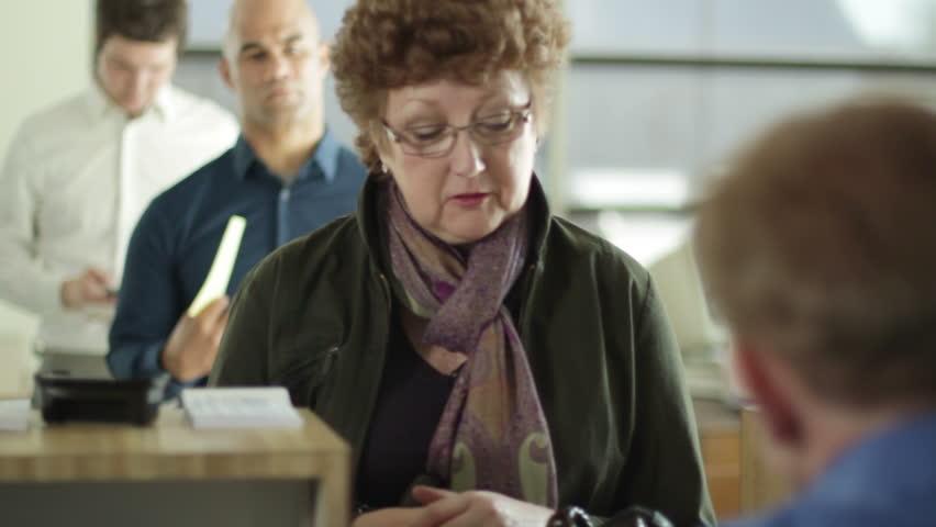 Female customer gets cash from bank teller. Over the shoulder shot from behind