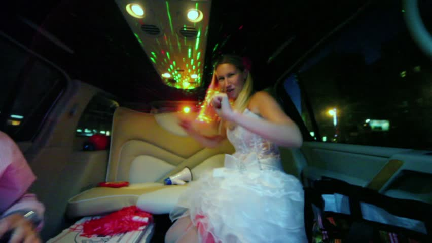 Bride in wedding dress dances and groom takes loudhailer during ride in limo