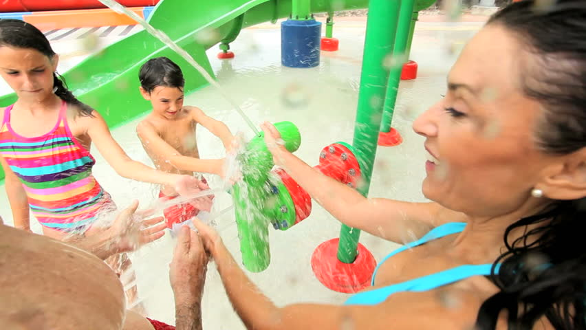 Happy Caucasian family enjoying their day getting wet in water park