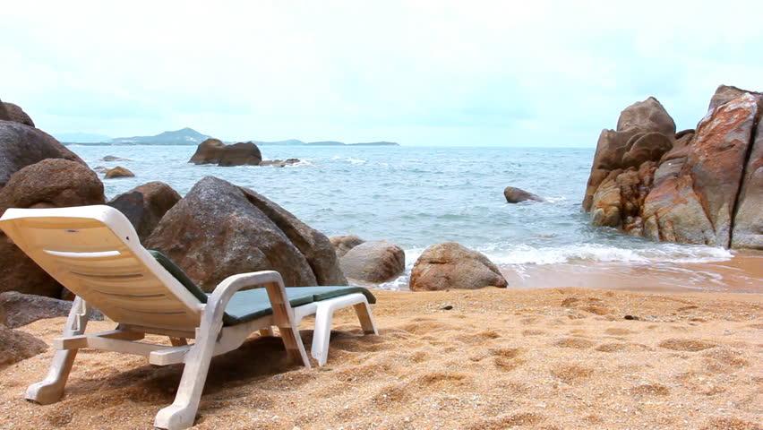 sunbed near water on a sandy beach hd stock footage clip - Beach Lounge Chairs