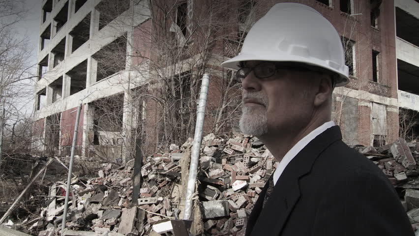 Developer walks into shot and looks around at the collapsed buildings around him, making notes. Big close up on developer, hand held camera.
