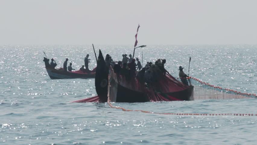 fishermen in boats pulling fishing nets - Kerala India