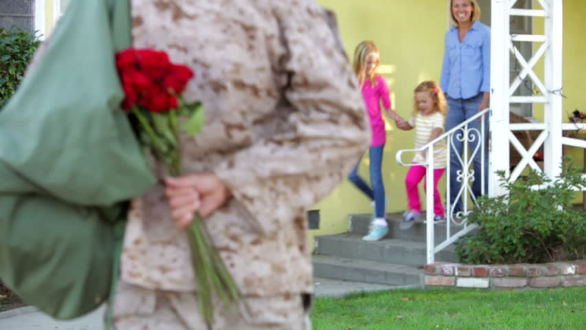 Family rushes to greet army husband returning on leave - he gives them flowers and they hug. Shot on Canon 5d Mk2 with a frame rate of 30fps