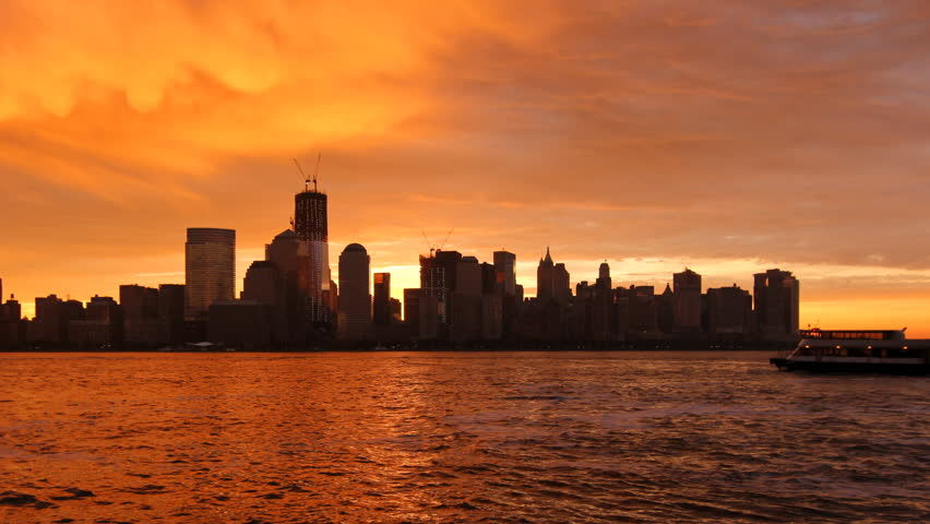 Sunrise over Lower Manhattan - Beautiful time lapse from night to day, with the sun appearing between the skyscrapers