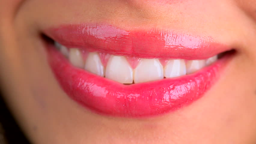 Extreme close up of lips blowing a kiss and smiling