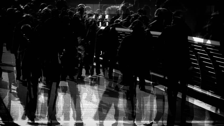 People walking -Multiple exposure of a crowd of backlit silhouetted people walking across Millennium Bridge in London