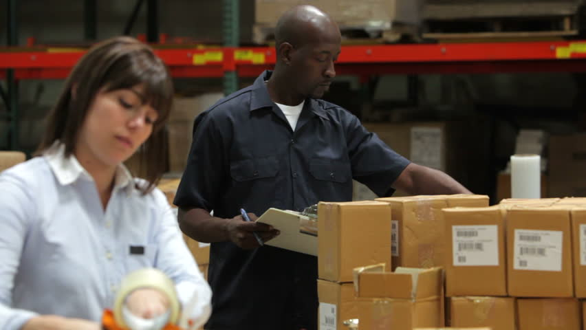 Focus starts on male factory worker checking boxes against clipboard then switches to foreground where female colleague is sealing packages for dispatch.