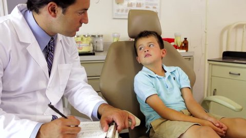 Dentist asks young male patient questions and writing down responses before asking him to show his teeth. Shot on Canon 5d Mk2 with a frame rate of 30fps