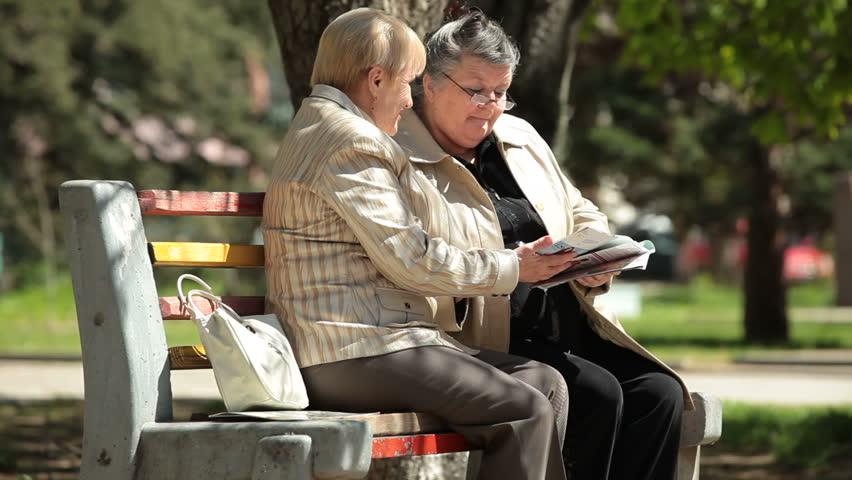 Senior Women Reading Magazines In The Park