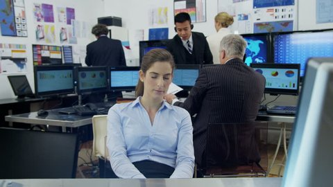A very bored and tired young businesswoman is struggling to stay awake at her desk while she is at work. As she lapses into sleep she looks around to check that her colleagues haven't noticed.