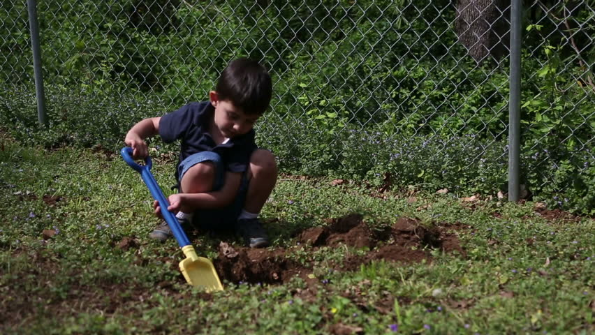 Male child digging a hole in the ground in the backyard