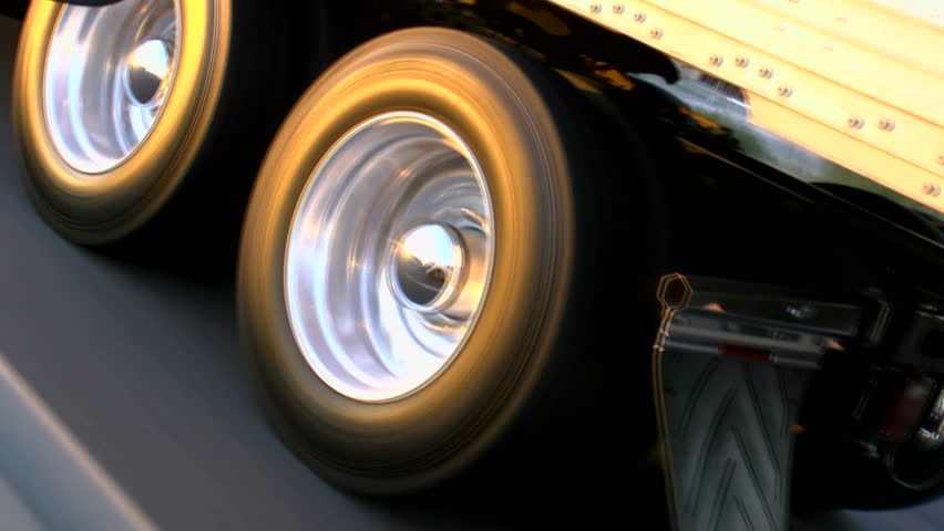Truck tire wheels spin, close up, glow in late afternoon sun as rig rides smooth, open highway. 1080p