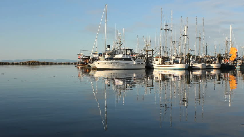 Early morning reflections in the calm water of Steveston Harbor, British Columbia, Canada where the commercial fishing fleet waits for the fishing season to open. Located near Vancouver.