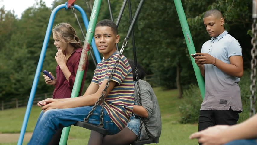 Teens on cell phones - Teenagers hanging out by some swings and using  mobile phones