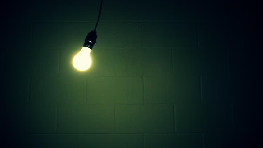 Light In Dark Room light bulb swaying against wall in dark room stock footage video