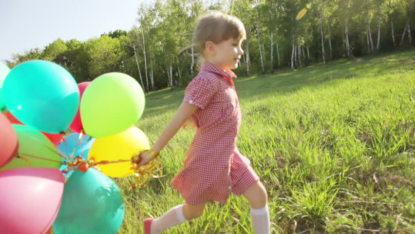 Child running with balloons in the park. Girl looking at camera