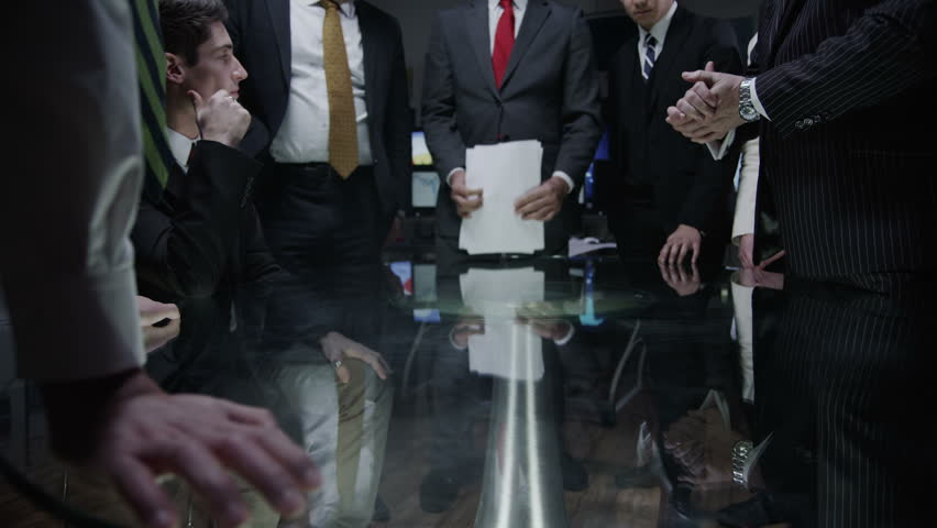 An imposing team of business professionals are having a  late meeting in a dark room full of computer screens. They are positioned around a large circular glass table and discussing ideas.