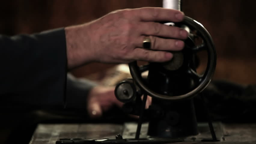 Close up shot of a tailor behind a sewing machine