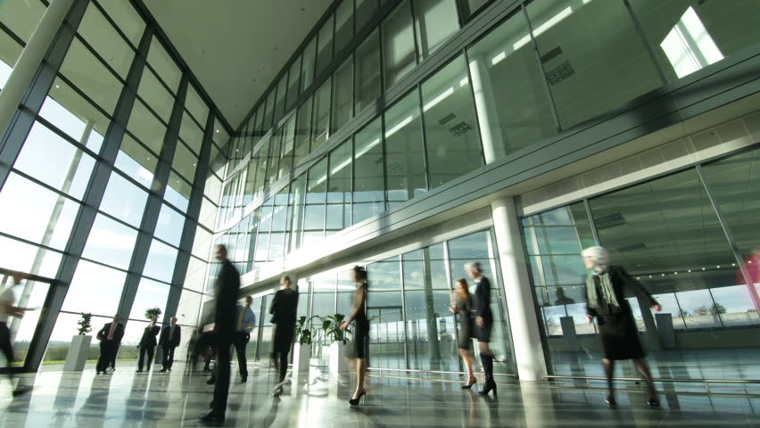 Time lapse of a large group business people moving around a large, open plan, glass fronted office building. The interior panels of glass are reflecting the clouds outside as they move across the sky. #3872081