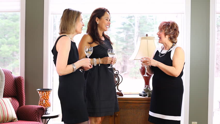 Three Mature Women Wearing Black Cocktail Dresses At A Party