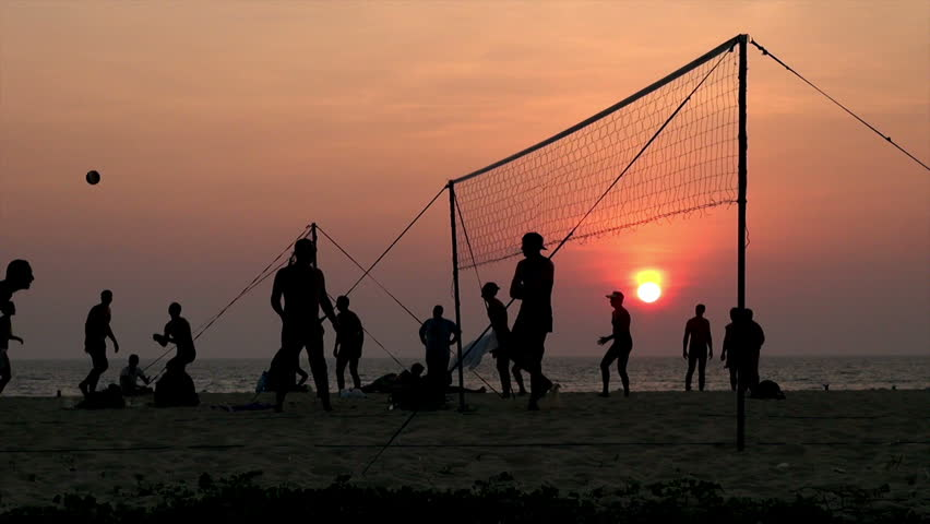bunch of people play beach volleyball at Karon Beach, Thailand / people enjoying beach volley at sunset