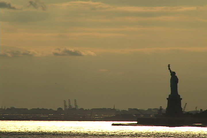 NEW YORK CITY - CIRCA SEPTEMBER 2001: Silhouette of Statue of Liberty at sunset with shimmering gold water in harbor. | Shutterstock HD Video #3884903