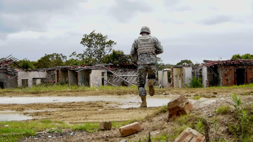 Ungraded shot of Army soldier running through ruins