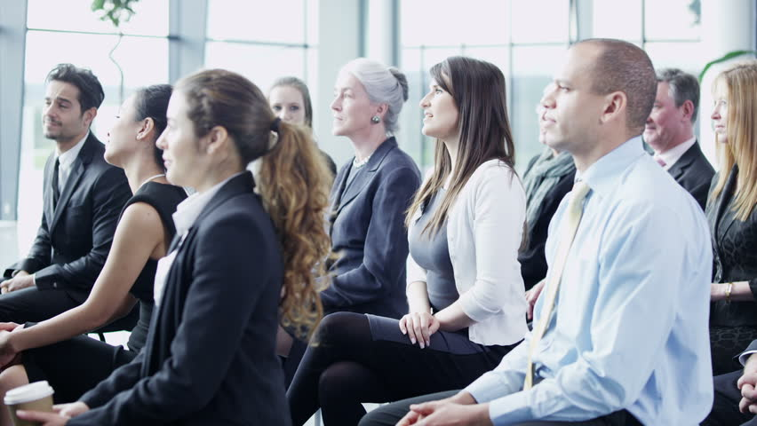 A multi ethnic group of business people of mixed ages are listening to a presentation at a business seminar and asking questions. | Shutterstock HD Video #3895643