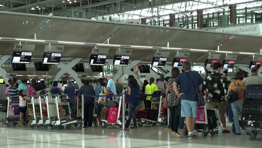 BANGKOK, THAILAND - 17 JUNE 2011 - Passengers wait at the check in queue in departure terminal of Bangkok Suvarnabhumi Airport. Bangkok Airport is one of the busiest international airports in Asia.