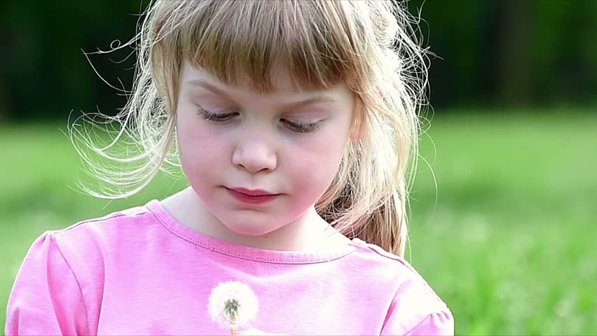 Little girl blowing dandelion in the park.High speed camera, slow motion