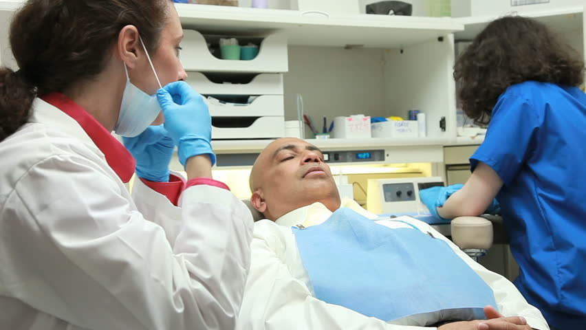 A Young Intern Talks To A Patient Sitting In The Dental Chair As ...