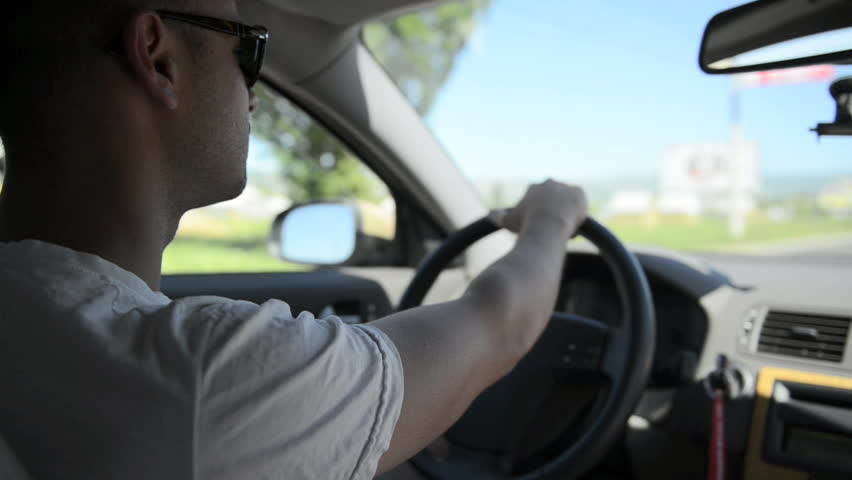Young man driving a car. Inside shoot