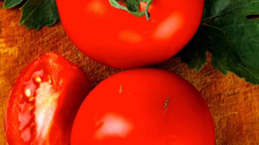 raw vegetables : some uncooked ripe fresh tomatoes over blue table on cutting board 1920x1080 intro motion slow hidef hd