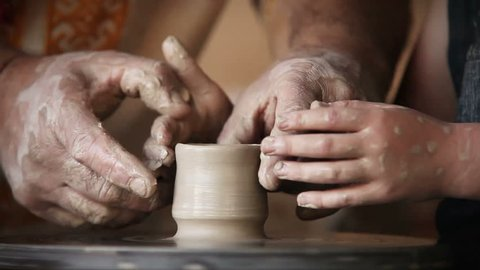 Hands of old potter and young pupil
