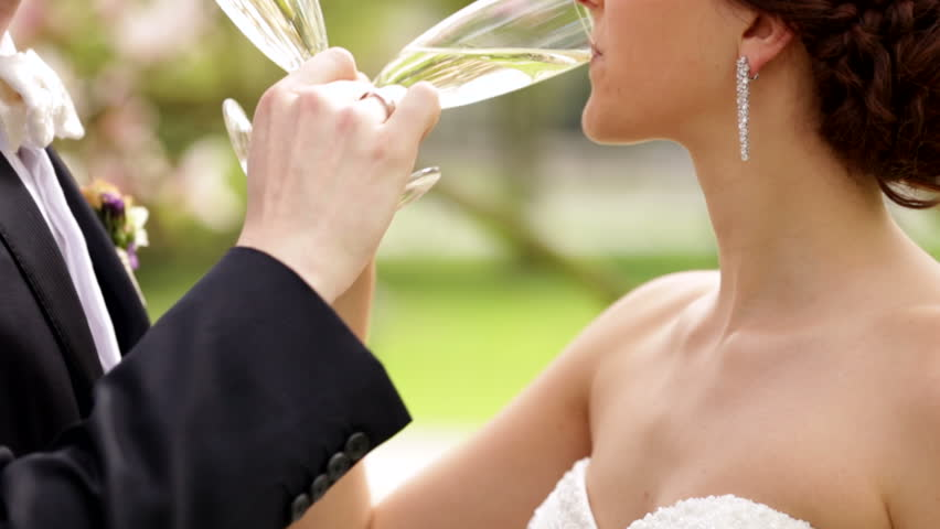 Newlyweds drinking champagne on their sunny wedding day