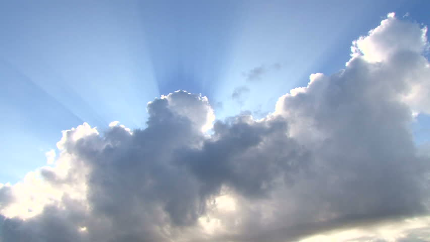 Beautiful cloudscape with large, building clouds and sunrise breaking through
