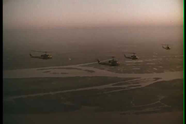 1960s - Good montage of helicopters flying in formation on a mission and landing in rice paddy.