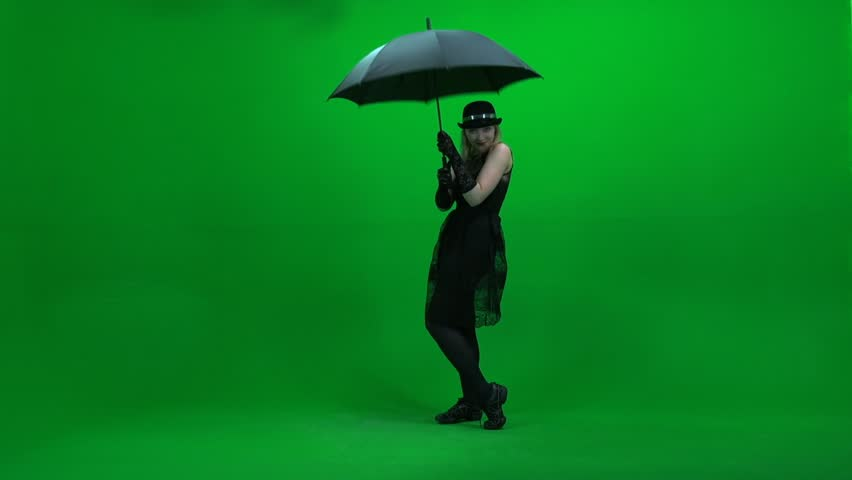 black dressed women dancing with umbrella isolated against green screen. female dancer. person people