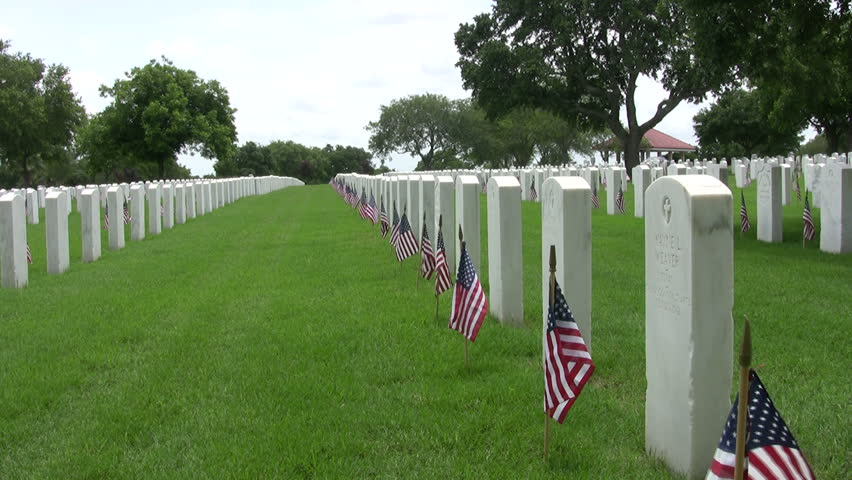 Video zoom in of the Fort Sam Houston Veterans Cemetery. Headstones and flags. Grass headstones flags. Memorial Day holiday.San Antonio, Texas. Don Despain of Rekindle Photo