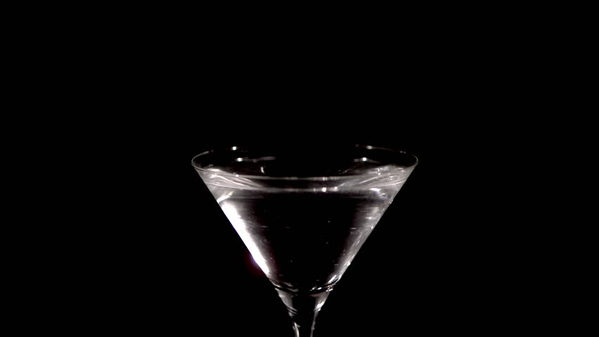 A fresh green olive on a cocktail stick is dropped in slow motion into a glass of martini, causing the drink to splash and spill. On a black background.