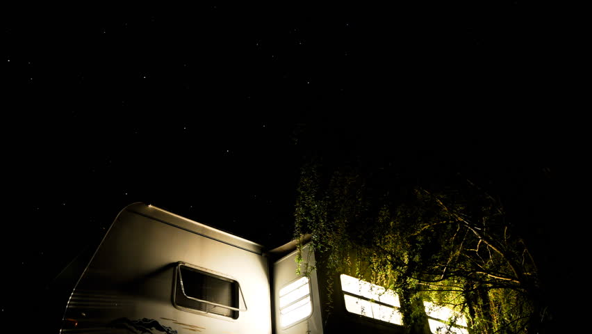 camper trailer sits under the stars as they go by and the lights go out (short)