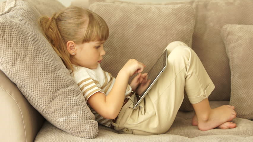 Little Girl Lying On The Couch With The Phone And Smiling