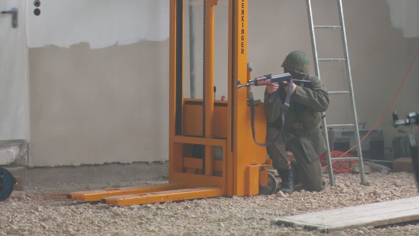 Femaile officer training with soldiers in warehouse