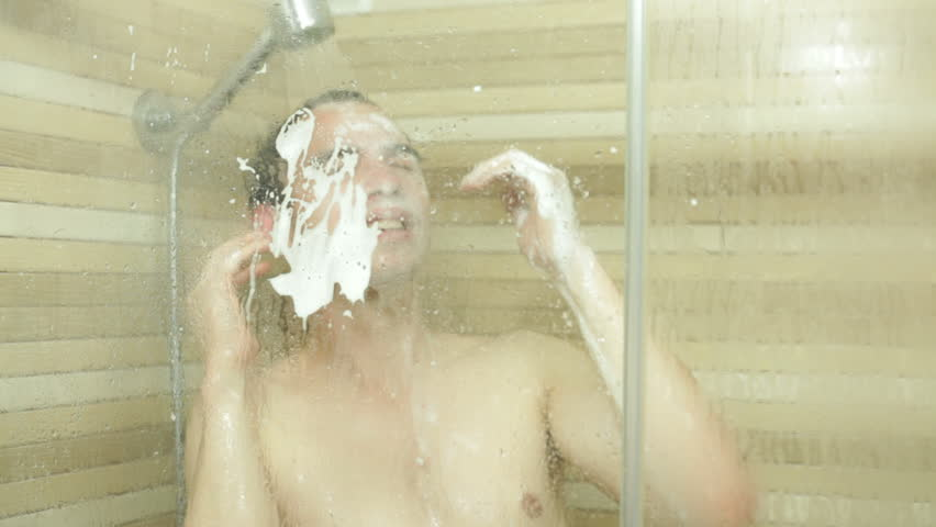 Young funny man washing his hair and face in shower
