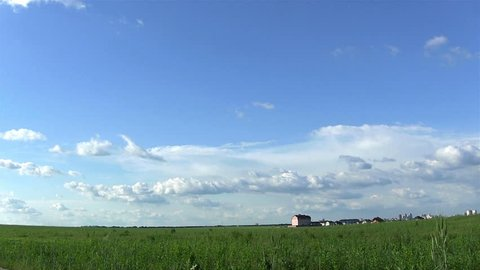 Clouds over field with the house. Timelapse
