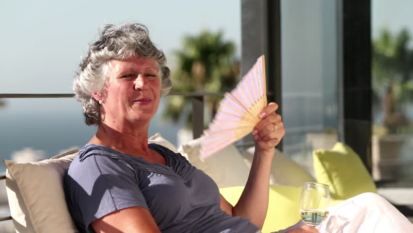 Mature woman feeling hot and fanning herself on the balcony
